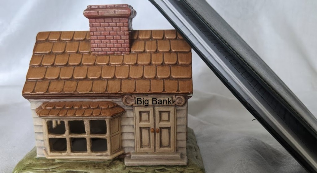 Model bank with a checkbook leaning against it.